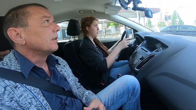 Anna sitzt neben Fahrlehrer am Steuer