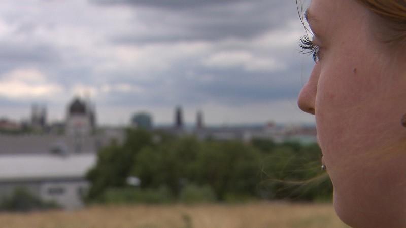 Anna schaut auf unscharfe Stadtsilhouette
